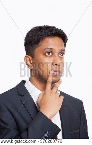 Contemplative young Asian businessman with hand on chin against white background