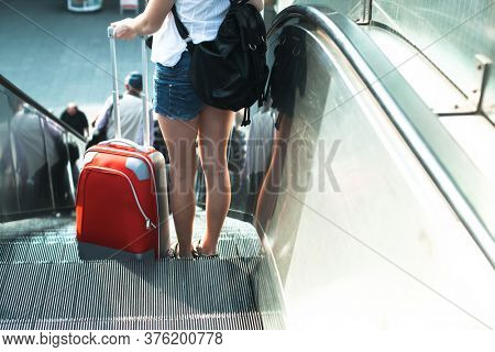 A girl with a suitcase goes down the escalator.