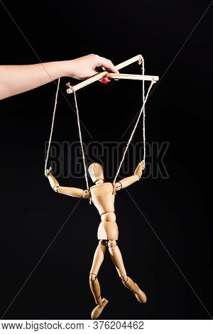 Cropped View Of Puppeteer Holding Wooden Marionette Isolated On Black