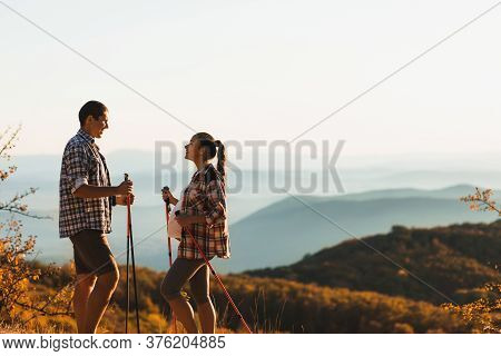 Young Pregnant Woman With Boyfriend Nordic Walking Outdoors With Trekking Poles. Active And Healthy