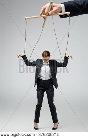 Cropped View Of Puppeteer Holding Businesswoman Marionette On Strings Isolated On Grey