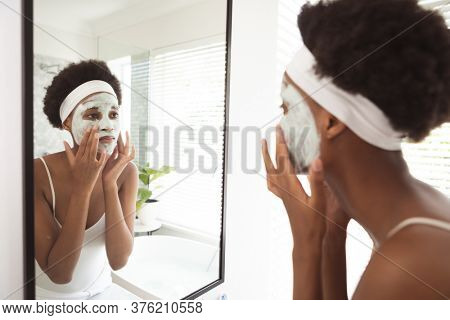 Mixed race woman spending time at home self isolating and social distancing in quarantine lockdown during coronavirus covid 19 epidemic, taking care of her skin in her bathroom.