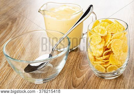 Spoon In Empty Bowl, Pitcher With Fruit Yogurt, Transparent Glass With Corn Flakes On Brown Wooden T