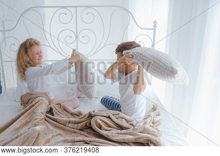 Two Children Holding Pillow Fighting Having Fun Together Playing In Bed Modern Bedroom Cozy Light Ho
