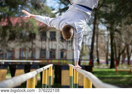 A Man Does Exercises On Uneven Bars On The Street. A Man Goes In For Sports.