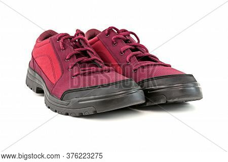 A Pair Of Simple Cheap Crimson Red Hiking Shoes Isolated On White Background - Perspective Close-up