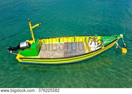 Small Fishing Boat Anchored In A Shallow Lagoon.