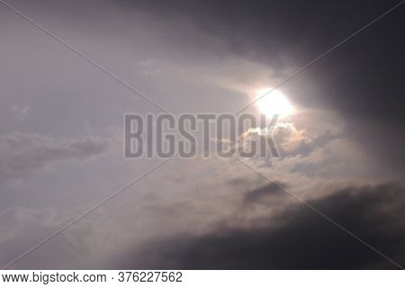 The Sun Looks Out From Behind The Clouds Before A Thunderstorm. Dark Gray Heavy Stormy Sky. Dramatic