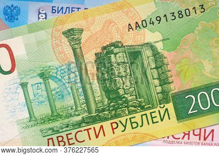 Russian Banknote 200 Rubles Lies On The Banknote 2000 Rubles. The Banknote Depicts The Sights Of Tau