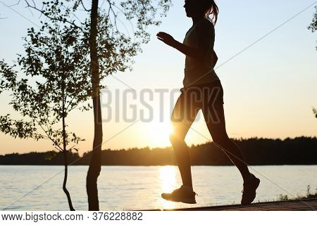 Sporty Female Jogger Running And Training Outside In Nature.