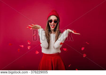 Graceful Girl In Fluffy Sweater Throwing Out Heart Confetti. Lovable Female Model In Red Skirt Danci