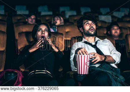 Audience Sitting In A Cinema And Watching Terrible Horror. Afraid Woman Sitting Near A Man Is Shock