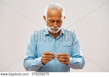 Portrait Of Serious Senior Man Who Is Decided To Quit Smoking.