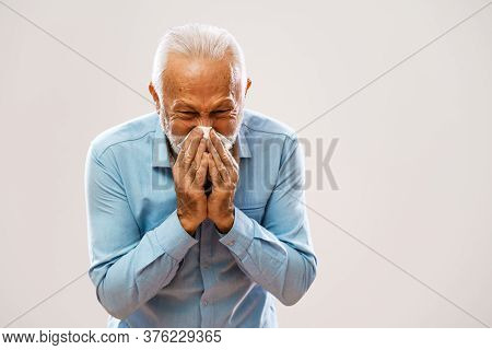 Portrait Of Senior Man Who Is Having Allergy And Blowing Nose.