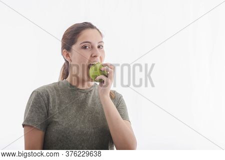 Beautiful Young Woman Biting A Delicious Looking Green Apple While Looking At The Camera.