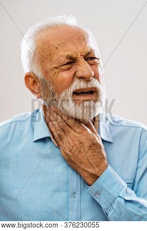 Portrait Of Senior Man Who Is Having Pain In Neck Glands.