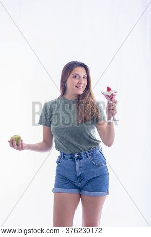 Young Woman Holding A Martini Glass With Strawberries And Whipped Cream And A Green Apple