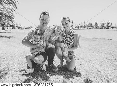 Happy Family Portrait Of Mother, Father, Son And Daughter Having Fun Together In The Park. Boy And L