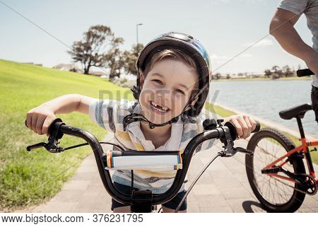 Portrait Of Cheerful Cute Kid With Helmet Riding His Bike At The Park
