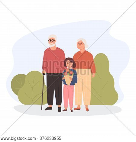 Trendy Grandparents With Granddaughter In Park Outdoors. Grandchild Holding A Flowers Bouquet For Gr