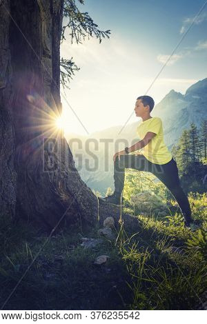 Sport Activities In The Nature Improve Health And Well-being. Active Young Athlete Running And Stret