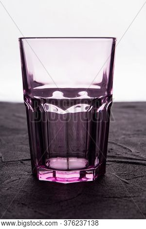 Empty Vintage Faceted Glass On A White Background. Close Up Clean Drinking Glass Cup On A Dark Grung
