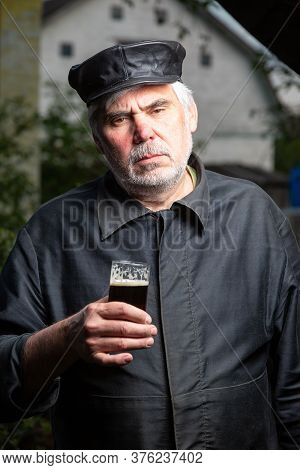 Serious Kind Sad Elderly Man With Black Old-fashioned Old Clothes And A Leather Cap With A Glass Of
