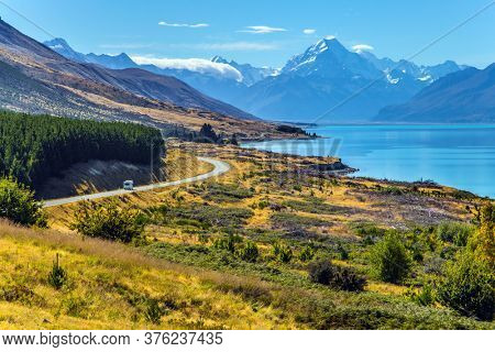 Mount Cook National Park. Magnificent highway runs along mountain lake with azure water to the snow-capped mountains. New Zealand. The concept of active, car and photo tourism
