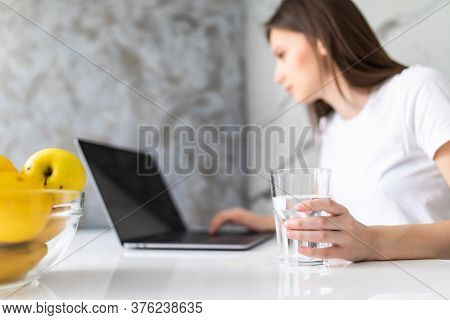 Woman Drinking From Water Glass While Typing At Her Laptop. Thirsty Woman Staying Hydrated While Wor