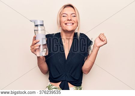 Young beautiful blonde woman drinking bottle of water over isolated white background screaming proud, celebrating victory and success very excited with raised arm