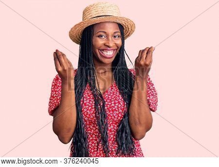 Young african american woman wearing summer hat doing money gesture with hands, asking for salary payment, millionaire business