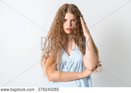 Photo Of Tired European Young Woman With Curly Long Hair, Holds His Hand Near His Head, Feels Fatigu