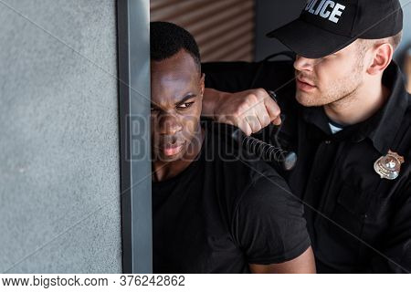 Selective Focus Of Police Officer In Uniform And Cap Holding Truncheon While Arresting African Ameri