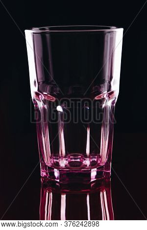 Glass For Water Or Alcoholic Drinks On Dark Background. Clean Empty Faceted Glass With Pink Hue.