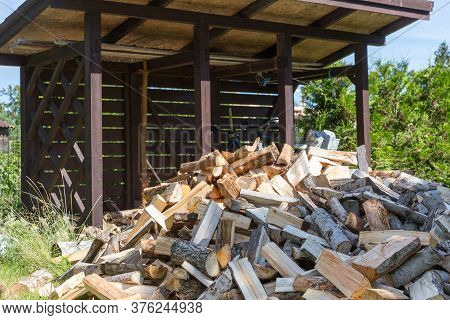 Firewood Harvested For Heating In Winter. A Pile Of Firewood In The Courtyard Of The House On The Gr