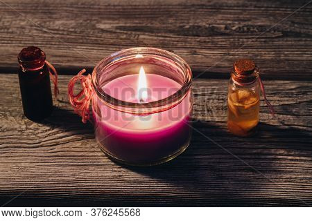 Concept Spa Therapy. Burning Candle And Two Small Oil Bottle On A Rustic Wooden Table.
