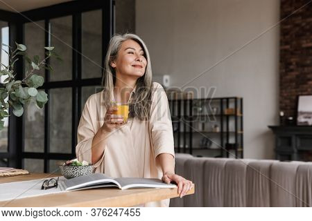 Photo of mature positive woman sitting at kitchen indoors at home while reading book and drinking juice.