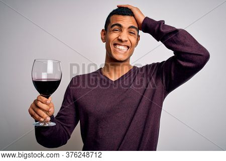 Handsome african american sommelier man tasting glass of red wine over white background stressed with hand on head, shocked with shame and surprise face, angry and frustrated. Fear and upset