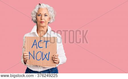 Senior grey-haired woman holding act now banner thinking attitude and sober expression looking self confident