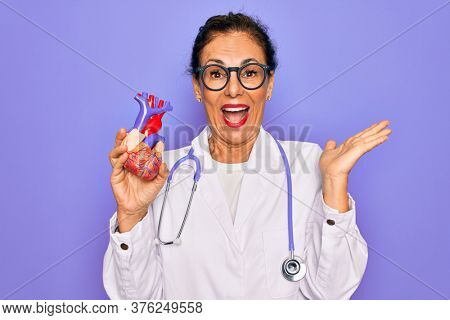 Middle age senior cardiologist doctor woman holding professional cardiology heart very happy and excited, winner expression celebrating victory screaming with big smile and raised hands