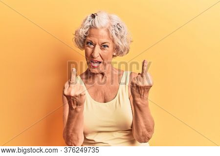 Senior grey-haired woman wearing casual clothes showing middle finger doing fuck you bad expression, provocation and rude attitude. screaming excited