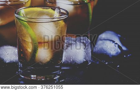 Alcoholic Cocktail Rum Cola With Ice, Lime, Lemon, Cola And White Rum, Dark Background, Selective Fo