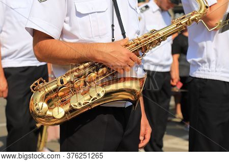 A Male Musician In A White Shirt Holds A Large Beautiful Golden Saxophone In A Column Of Military Mu