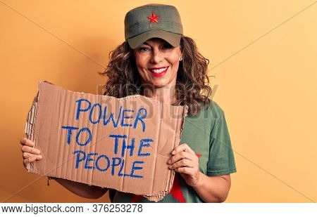 Middle age brunette communist woman holding banner with power to the people message looking positive and happy standing and smiling with a confident smile showing teeth