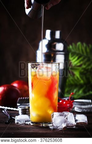 Summer Tequila Sunrise Cocktail With Silver Tequila, Grenadine Syrup, Orange And Ice Cubes. Wooden B