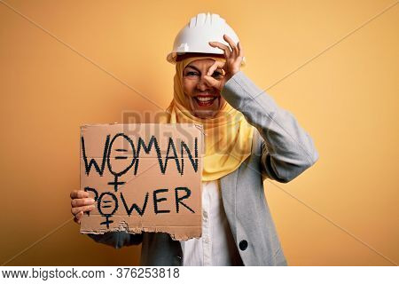 Middle age architect woman wearing muslim hijab holding banner with women message with happy face smiling doing ok sign with hand on eye looking through fingers