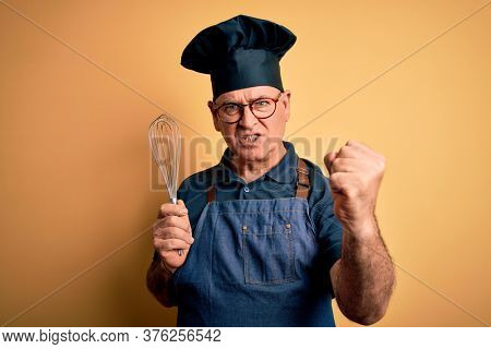 Middle age hoary cooker man wearing apron and hat holding whisk over yellow background annoyed and frustrated shouting with anger, crazy and yelling with raised hand, anger concept