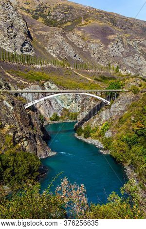 Incredible Adventures in New Zealand. The river is bright green. River and old bridge Kawarau between Queenstown and the town of Cromwell. The concept of extreme, active and photo tourism