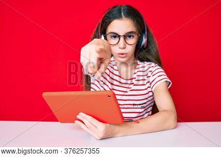 Cute hispanic child girl using touchpad and headphones sitting on the table pointing with finger to the camera and to you, confident gesture looking serious