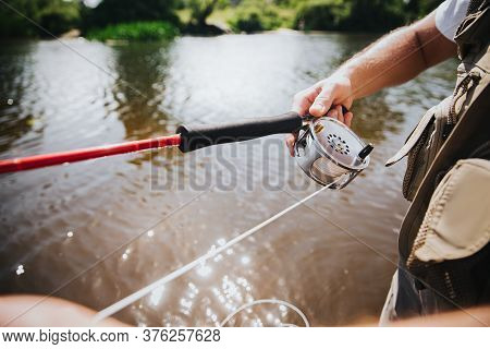 Young Fisherman Fishing On Lake Or River. Cut View Of Rod In Guys Hand. Professional River Hobby. Ca